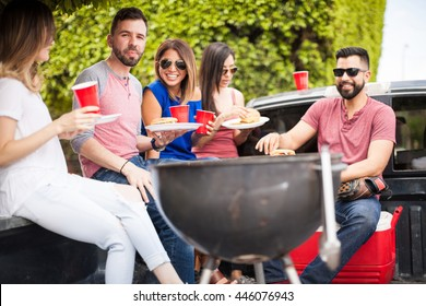 Group of friends sitting on a pick up truck and eating cheeseburgers and drinking beer next to a grill