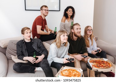 Group of friends sitting on sofa and spending time together while playing video games,eating pizza and drinking beer at home