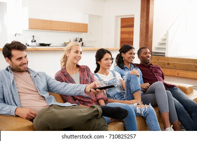 Group Of Friends Sitting On Sofa Watching Television Together