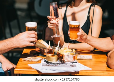 Group of friends sitting on a summer terrace with beer and wine in their hands and snacks on the table