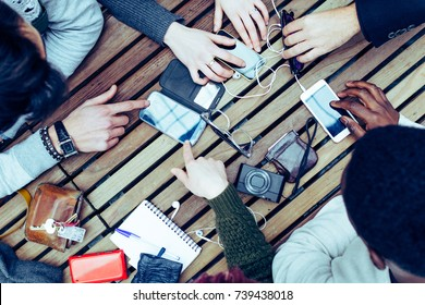 Group of friends sitting on the table with smart devices and speaking. Social addicted people sharing ideas and having fun together. Top view of teamwork connected with Wifi on meeting table in a bar