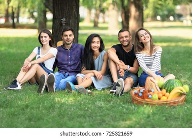 Group of friends sitting in park on grass and looking at camera. Men and women rest on nature with guitar and enjoy life. Young beautiful people outdoors on sunny day