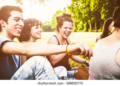 Group of friends sitting in park and spending time together in sunny day