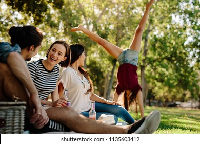 Group of friends sitting at park with a woman doing a cartwheel jump in background. Young man and women enjoying a summer day at park. Friends enjoying picnic.