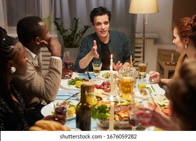 Group of friends sitting at the table and listening to young man who talking during holiday dinner