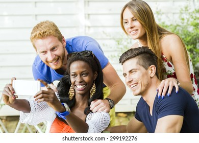 A group of friends sitting a table and talking smiling  while taking selfies on a hot summer day
