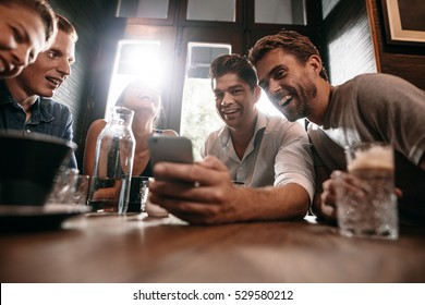 Group of friends sitting together in a cafe looking at smart phone and smiling. Young guy showing something to his friends on his cell phone.
