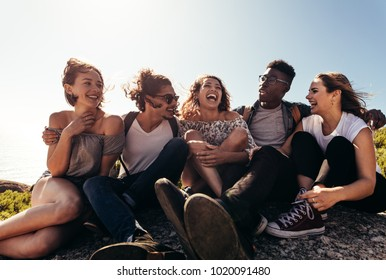 Group of friends sitting together on mountain top and enjoying themselves. Young men and women enjoying on their holiday outdoors.