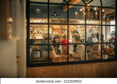 Group of friends sitting together at a table by windows inside of a trendy bar ordering drinks from a waitress