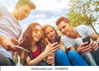 Group of friends sitting together using their mobile phones