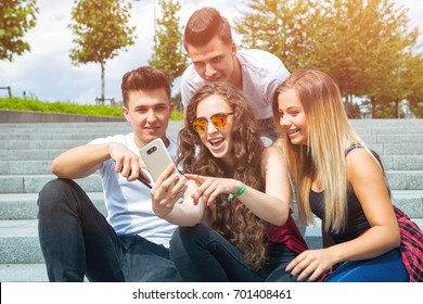 Group of friends sitting together using mobile phone and laughing