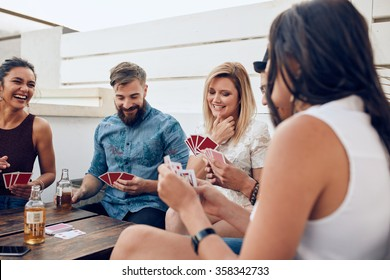 Group of friends sitting at a wooden table and playing cards. Young people playing a game of cards during a party.
