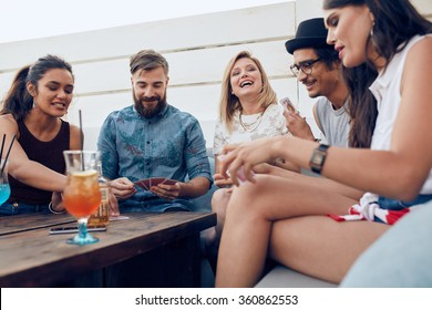 Group of friends sitting at a wooden table and playing cards. Cheerful young people partying together and playing cards.