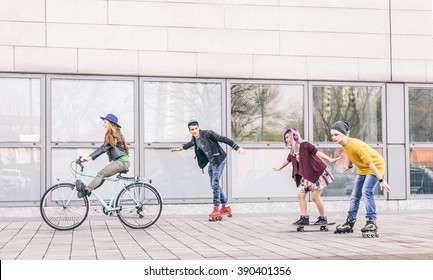 Group of friends skating and cycling in an urban area - Cheerful teenagers having fun outdoors