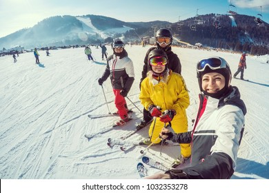 Group of friends with ski on winter holidays skiers having fun on the snow