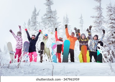 Group of friends skiers and snowboarders having fun on snowbound winter forest. Sheregesh resort, Siberia, Russia