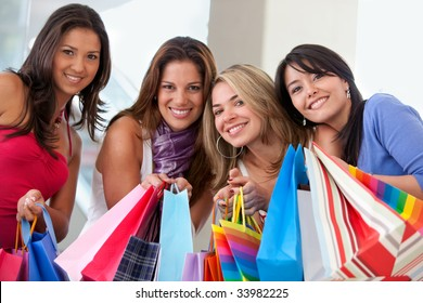 group of friends smiling with shopping bags in a mall