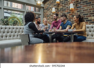 Group of friends are socialising over coffee in a bar/restaurant.