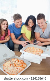 A group of friends with some pizza as one guy reaches out for a slice