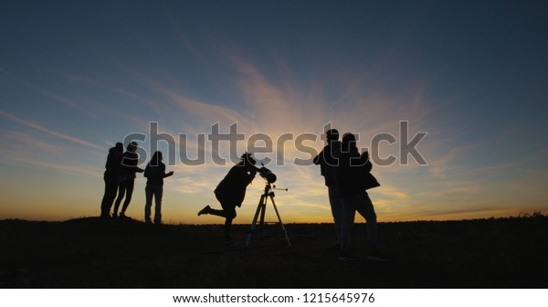 Group of friends spending time on coast and looking through telescope in dark twilight against sunset sky