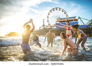 Group of friends splashing water while swimming in the sea - Multi-ethic group of people having fun on the beach