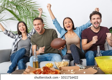 Group of friends sport fans watching rugby match cheering team