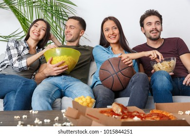 Group of friends sport fans watching basketball game eating snacks