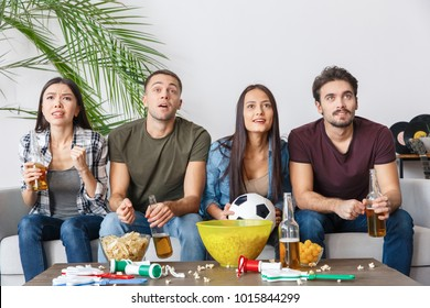 Group of friends sport fans watching football match concentrated