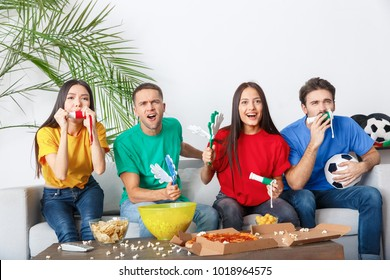 Group of friends sport fans watching match in colorful shirts holding noisemakers