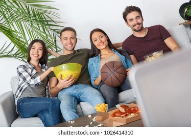 Group of friends sport fans watching basketball game looking camera