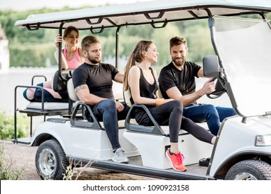 Group of friends in sports wear having fun driving a golf cart near the lake