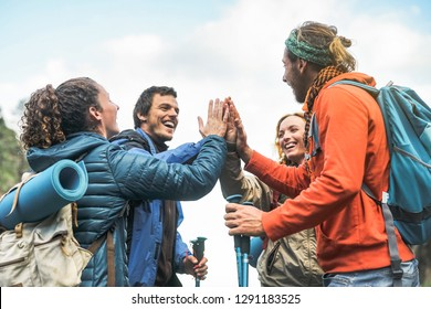 Group of friends stacking hands on peak of mountain - Young tourists trekking and exploring the wild nature - Trekker, team, hike and travel people concept