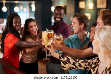 Group Of Friends Standing At Bar And Making A Toast On Night Out
