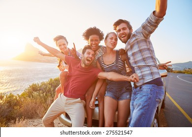 Group Of Friends Standing By Car On Coastal Road At Sunset