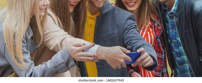 Group of friends standing by the wall background and enjoying each other- Teenagers using smartphone and smiling while trying to take a selfie- Technology concept