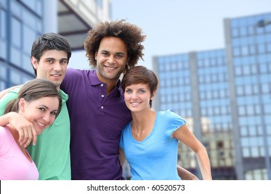 Group of friends standing in front of modern buildings in  town