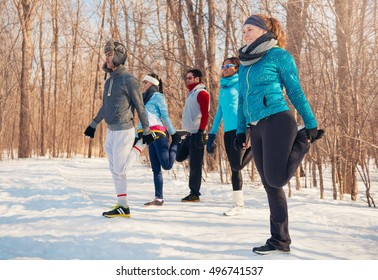 Group of friends stretching in the snow in winter