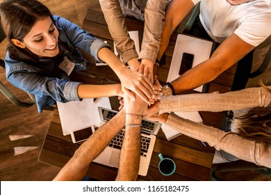 Group of friends studying together and making a high five