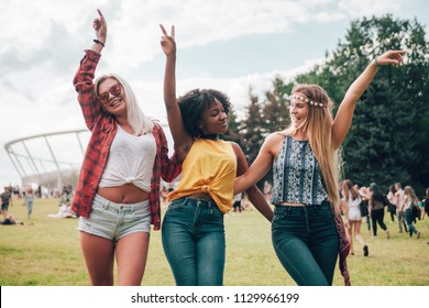 Group of friends at summer music festival having fun together