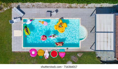 Group of friends sunbathing on cool air matress in a swimming pool, view from above - Pool party, people relaxing and enjoying summer