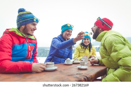 group of friends take a break in a mountain chalet. Eating hot chocolate and cakes