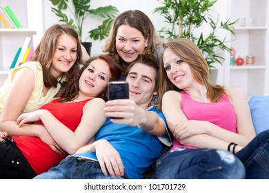 group of friends taking a picture of themselves on cell phone