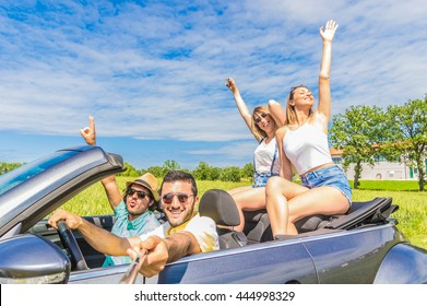 Group of friends taking a selfie at car trip around Europe. Four caucasian people having fun on a sportive car outdoor.