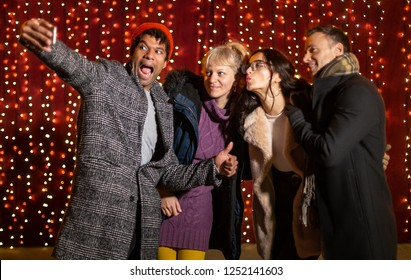 Group of friends  taking selfie in front of light wall at Christmas market.