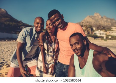 Group of friends taking selfie on the seashore. Young people having great time together at the beach.