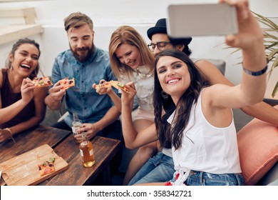 Group of friends taking selfie on a smart phone. Young people eating pizza on rooftop party taking selfie.