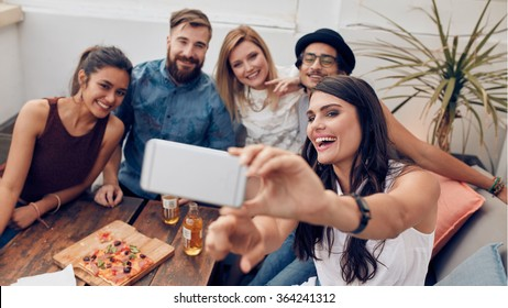 Group of friends taking selfie on a smart phone. Young man and women taking a self portrait on cell phone. Young people on rooftop party, capturing the moment on camera.