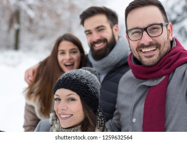 Group of friends taking selfie in snowy forest, enjoying winter holidays
