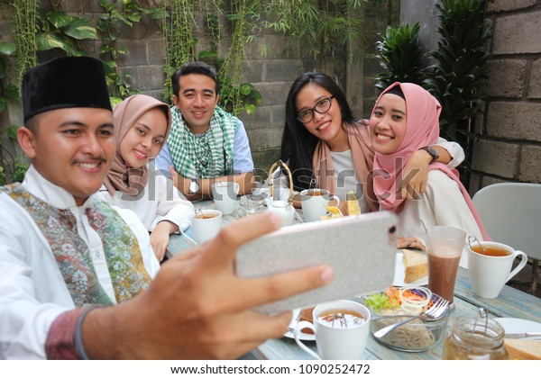 group of friends taking selfie at table dining during ramadan celebration