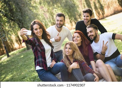 Group of friends taking selfie in urban park. Five young people wearing casual clothes.